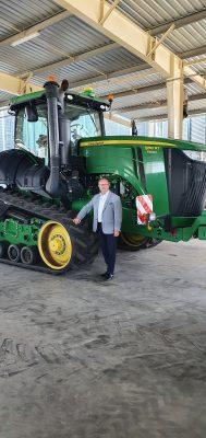 Józef Śliwa stoi przy maszynie rolniczej.